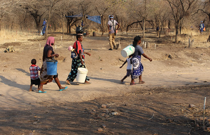 Beneficiaries from Gomo Village, Zimbabwe, on their way to fetch water, pass through an access route on a minefield being cleared by HALO Trust. Photo credit: HALO Trust, 2015