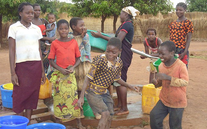 Children gather around a water pump in Niassa province, Mozambique. The Irish Aid programme has tackled malnutrition in Niassa through support to agricultural research; water, sanitation and hygiene (WASH); and community health structures.