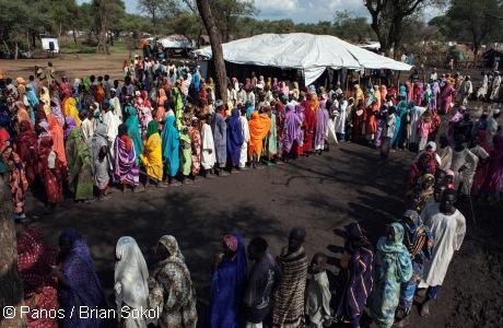 Sudanese refugees queue for blankets and mosquito nets at a distribution point in Yusuf Batil Refugee Camp. Photo: Panos / Brian Solol