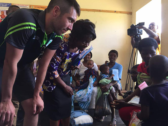 Ireland cricketer Andrew Balbirnie meets with mothers and children at the Rutope Clinic, Bindura, Zimbabwe