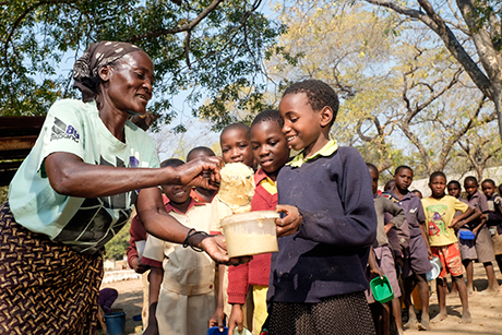 During the Zimbabwe food crisis, a local volunteer cooks and hands out porridge to Surprise (age 10) at a village school where 150kg of healthy corn-soya blend is provided by NGO partners each day. 28/07/16 Photo Credit: Trócaire